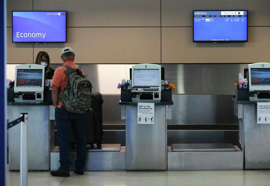 A traveler checks in at the United counter as a screen shows the limited amount of flights. The coronavirus pandemic has meant airlines have cut back on direct flights from midsize, nonhub airports like San Antonio. Photo: Kin Man Hui /Staff Photographer / **MANDATORY CREDIT FOR PHOTOGRAPHER AND SAN ANTONIO EXPRESS-NEWS/NO SALES/MAGS OUT/ TV OUT