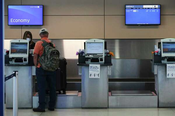 A traveler checks in at the United counter as a screen shows the limited amount of flights. The coronavirus pandemic has meant airlines have cut back on direct flights from midsize, nonhub airports like San Antonio.