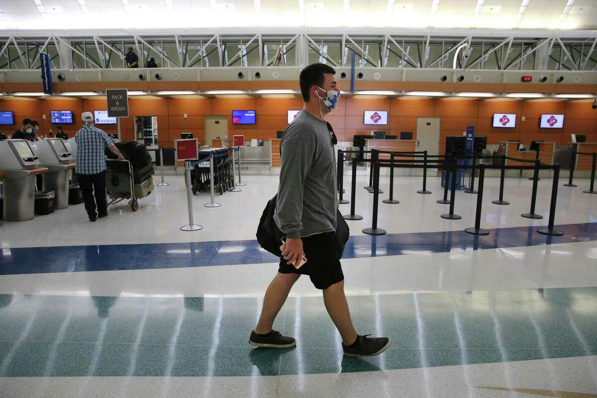 Reed Buce wears a mask as he walks to his flight's gate on Monday, May 18, 2020. Travelers at San Antonio International Airport are still a fraction of the numbers pre-COVID-19 but the few who are traveling by plane are often essential workers or coming to aid of loved ones. Data shows there has been a slight pickup of passengers as stay at home orders have been limited.