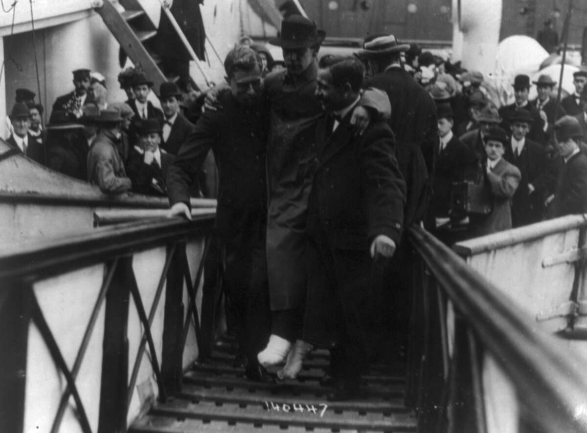 Harold Bride, surviving wireless operator of the HMS Titanic, with feet bandaged, being carried up ramp of ship, c. May 27, 1912.