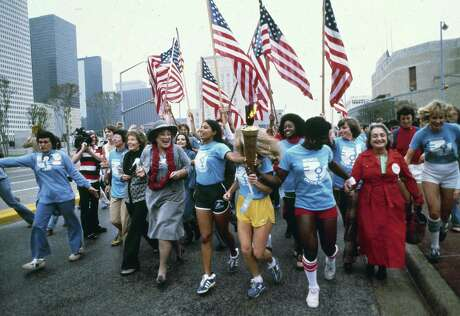 ADVANCE FOR USE MONDAY, JUNE 20, 2016 AND THEREAFTER -FILE - In this November 1977 file photo, leaders of the women's movement pass a torch that was carried by foot from New York to Houston, Texas for the National Women's Convention. Among the marchers, from left foreground are tennis star Billie Jean King, in blue shirt and tan pants; former U.S. Congresswoman Bella Abzug, wearing a hat; and feminist writer Betty Friedan, in a red coat. (AP Photo/Greg Smith)