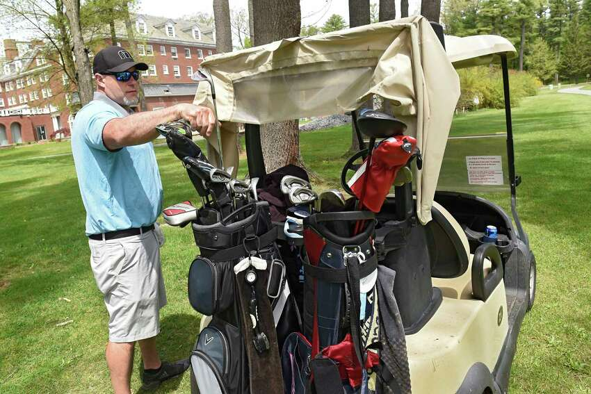 Eric Cushing of Ballston Spa puts away a club in his bag on a golf cart while playing a round with friends at Saratoga Spa Golf Course on Tuesday, May 19, 2020 in Saratoga Springs, N.Y. Carts are now permitted under the latest Empire State Development guidance. (Lori Van Buren/Times Union)