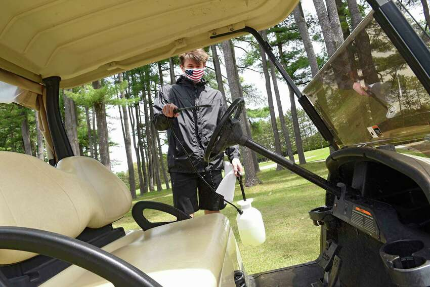 Employee Brian Hart disinfects a golf cart at Saratoga Spa Golf Course on Tuesday, May 19, 2020 in Saratoga Springs, N.Y. Carts are now permitted under the latest Empire State Development guidance. (Lori Van Buren/Times Union)