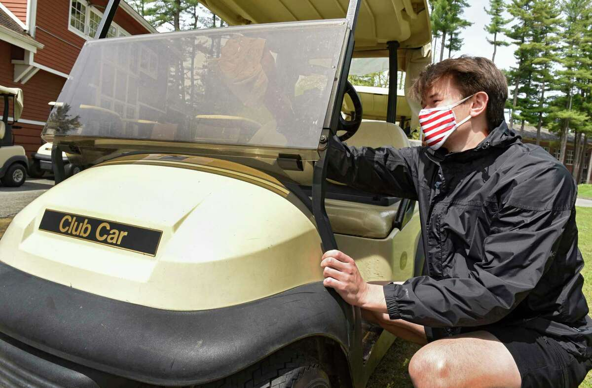Employee Brian Hart wipes down the windshield as he disinfects a golf cart at Saratoga Spa Golf Course on Tuesday, May 19, 2020 in Saratoga Springs, N.Y. Carts are now permitted under the latest Empire State Development guidance. (Lori Van Buren/Times Union)