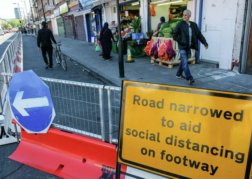 On London's Seven Sisters Road on May 19, a sign indicates that the road has been narrowed to vehicles to allow those walking on the sidewalk more space for social distancing.
