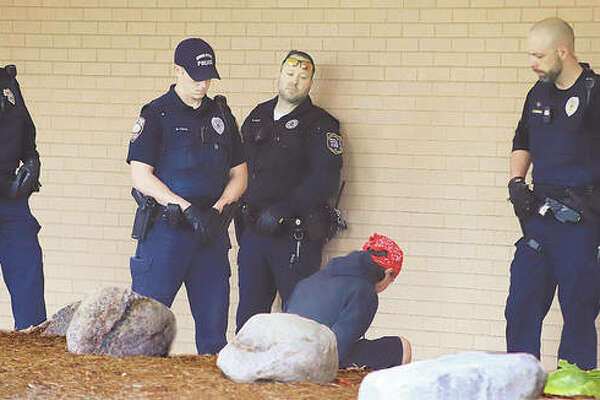 "Some of the many Wood River and East Alton Police officers who responded to the Madison County Building in Wood River hover over a man detained for a while after he allegedly pulled out a BB gun when an officer approached him for sleeping near the Madison County Health Department. The gun prompted the officer to put out a radio call code for a ""subject with a gun"" and virtually every officer in both towns responded."