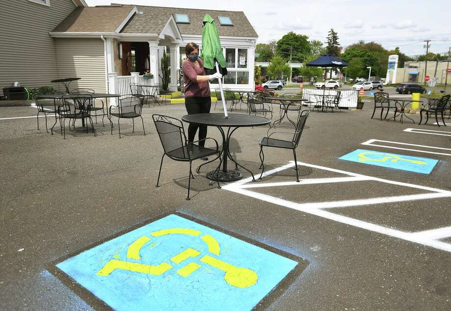 Gusto Trattoria employee Ariana Grabowski sets up an outdoor dining area in the parking lot of the restaurant Monday in preparation for Wednesday's phase one reopening in Milford. Photo: Brian A. Pounds / Hearst Connecticut Media / Connecticut Post