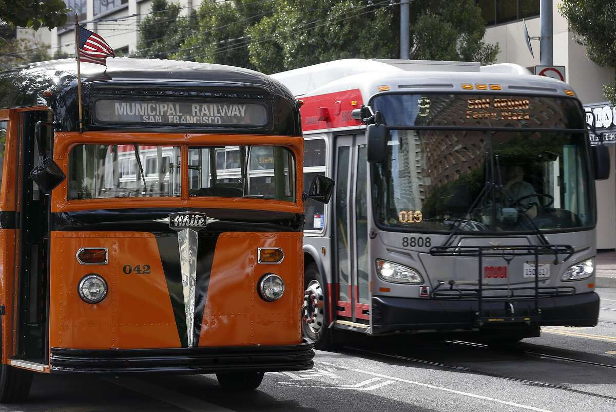A modern day 9-San Bruno Muni bus rolls past a vintage 1938 White Motor Company bus which was providing free rides during the Muni Heritage Weekend celebration in San Francisco, Calif. on Saturday, Sept. 7, 2019.