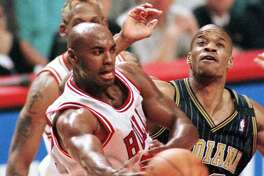 Scott Burrell passes off near the basket in front of teammate Dennis Rodman, partially hidden, and the Pacers' Antonio Davis during Game 5 of the Eastern Conference Finals in 1998.