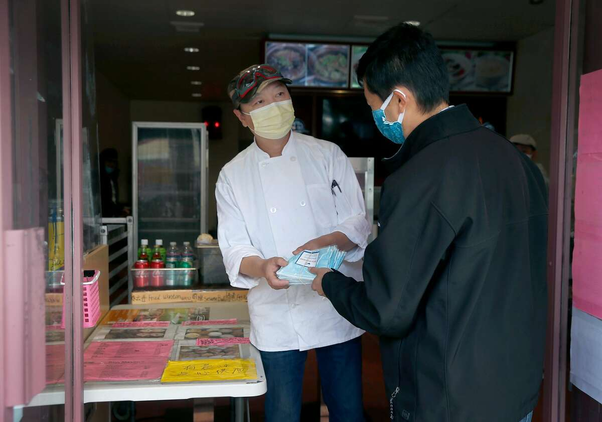 Seeyew Mo (right), a volunteer for Communities As One, hands out protective masks to Sun MaximÍs Bakery owner Tony Lee on Irving Street in San Francisco, Calif. on Tuesday, May 19, 2020. Communities As One is distributing PPE, groceries and other essential items to restaurant workers and Asian seniors who are at a greater risk of contracting the COVID-19 coronavirus.