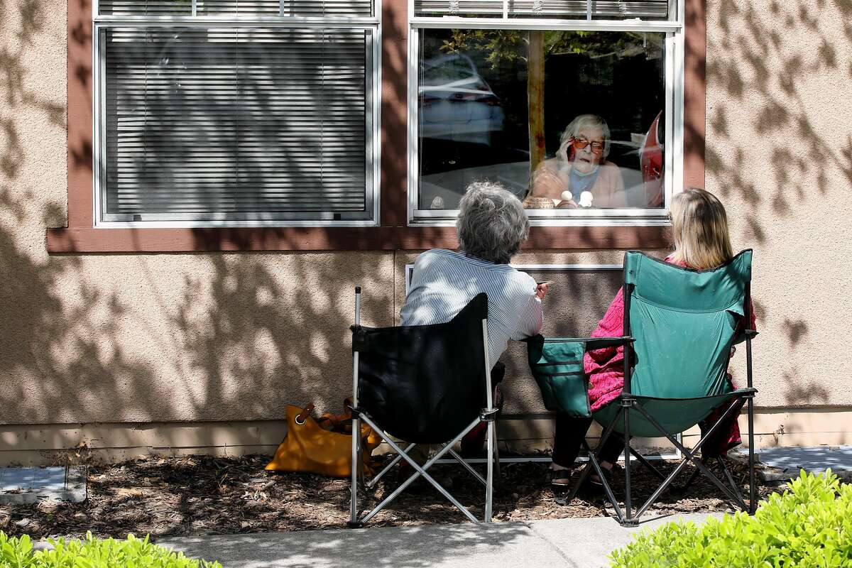 Berkeley Councilwoman Kate Harrison, right, and husband Jim Hendry (cq'd) visit her 96-year-old mother, Toni Gardner, in front of her window at Westmont of Pinole, located at 2850 Estates Ave., on Friday, May 8, 2020, in Pinole, Calif. Gardner has lived at the assisted living facility since December. Last Friday evening, Westmont called and said one person had tested positive. The facility had contacted the county and requested for testing to be done, but were told no. The county allegedly said that since only one person had tested positive, there was no urgent need for mass testing to be done. Since then, Harrison launched a crusade to implement testing at these facilities in Contra Costa County. And mostly, she's won.