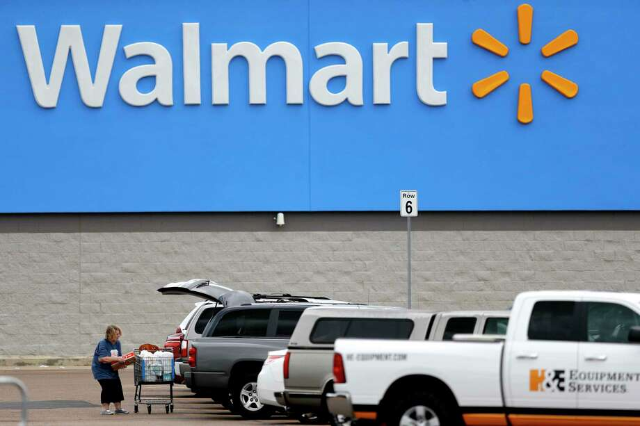 FILE - In this March 31, 2020 file photo, a woman pulls groceries from a cart to her vehicle outside of a Walmart store in Pearl, Miss.  Walmart became a lifeline to millions of people as the coronavirus spread, and its profit and sales surged during the first quarter, topping almost all expectations.  (AP Photo/Julio Cortez, File) Photo: Julio Cortez / Copyright 2020 The Associated Press. All rights reserved.