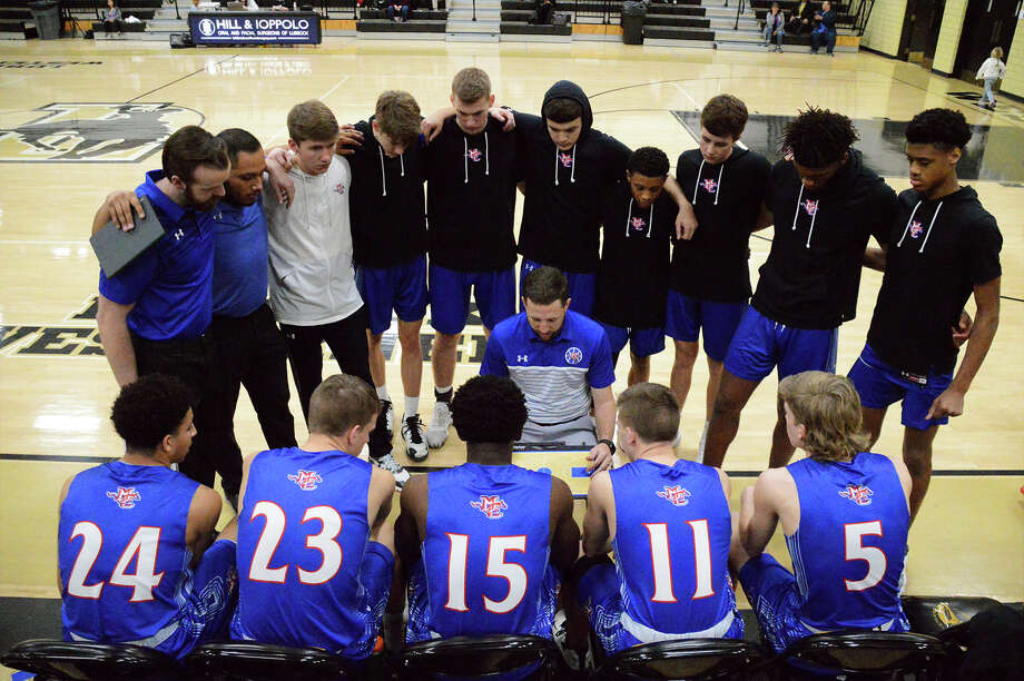 Midland Christian assistant boys basketball coach Trent Langford, center, diagrams a play for his players on the bench. Courtesy photo/Khloe Scott