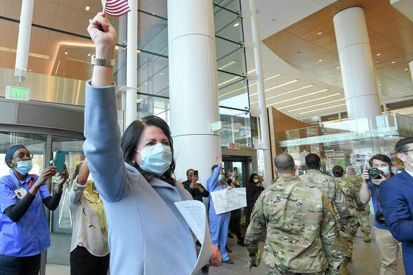 Kathleen Silard, president and CEO of Stamford Hospital, waves a flag as she watches military personnel leave.