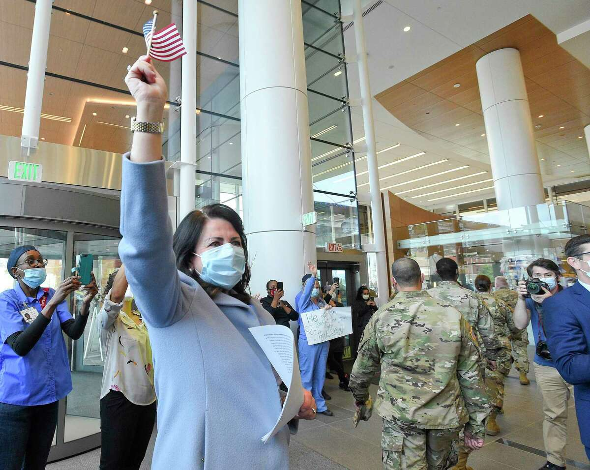Kathleen Silard, President & CEO of Stamford Heath, waves a flag as she watches military personnel making up Task Force 811-1 of the Connecticut National Guard and U.S. Army Reserves Urban Augmentation Medical Task Force as they parade through cheers from staff at Stamford Hospital on May 19, 2020 in Stamford, Conn. Stamford Health, which includes Stamford Hospital, is the Stamford Chamber of Commerce's 2020 Company of the Year.