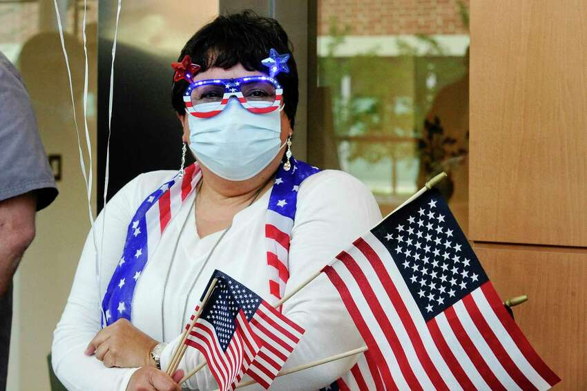 Annette Nieves, a respiratory therapist dawns her RED, Whit, and Blue spirit as she waits to salute military personnel making up Task Force 811-1 of the Connecticut National Guard and U.S. Army Reserves Urban Augmentation Medical Task Force (UAMTF) preparing to leave in a parade through the cheers and salutes of Thank You's from the Doctors, Nurses, support staff amd administrators of Stamford Hospital on May 19, 2020 in Stamford, Connecticut. The military support from branches of the U.S. Army, Navy and Air Force Resevres from throughout the United States, as well as units of the Connecticut National Guard, spent six weeks at the hospital supporting, treating and caring for patients during the COVID-19 Pandemic.