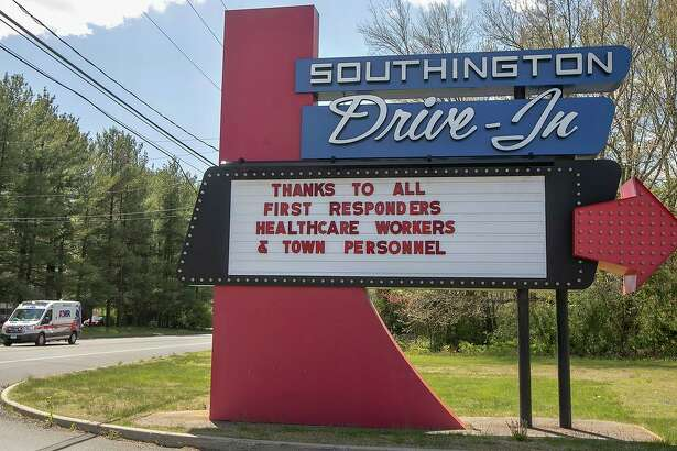 In this Tuesday, May 12, 2020, photo, the Southington Drive-In displays a message to first responders, healthcare workers and town personnel as an ambulance heads to a call on Meriden Waterbury Turnpike in Southington, Conn. (Dave Zajac/Record-Journal via AP)