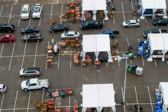 Food is distributed from tents to hundreds of cars waiting in line to receive food from a pickup site April 18 in a parking lot adjacent to NRG Stadium. Houston ISD and the Houston Food Bank, which hosted the event, are holding their final mass distribution site at the stadium on Friday.