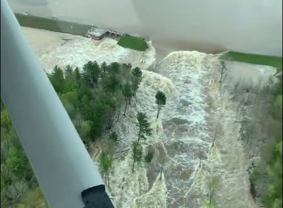 The Tittabwassee River spills over the damaged Edenville Dam in this screenshot of video shot by Ryan Kaleto on Tuesday, May 19 2020. Photo: Screenshot Of Video By Ryan Kaleto