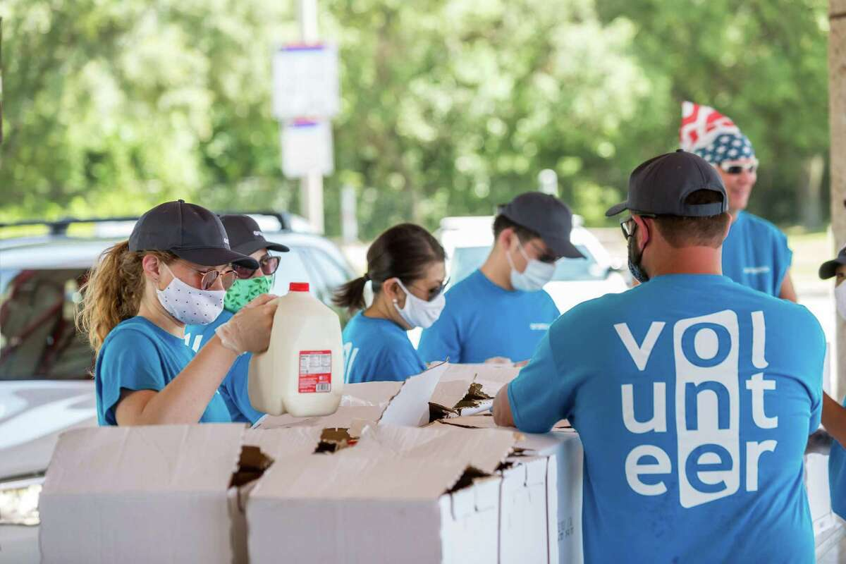 Aramco Americas volunteers prepare food to be distributed for the Houston Food Bank at the former Park and Ride facility on Pinemont, which serves 2,200 families in northwest Houston.The volunteers packed up free groceries, masks and hand sanitizer. The event was hosted by Texas State Representative Anna Eastman and Harris County Precinct 4 Commissioner Jack Cagle.