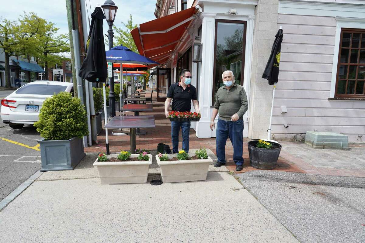 New Canaan is starting to reopen its stores on Wednesday, May 20, but dining outside of restaurants is going to wait until Friday, May 22. Spiga restaurant's owner Gino Racenlli stands outside with Luis Narvaez, who is holding the flowers, on Tuesday, May 19. Many owners have signs asking patrons to wear masks as they reopen amid the coronavirus pandemic.