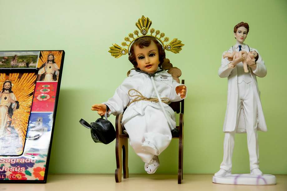 Traditional religious figures adorned in doctor's garb are seen along the wall of an exam room at Dr. Carlos Ramírez's Terra Nova Medical Group clinic, where he sees uninsured patients, many of them undocumented. Photo: Jessica Christian / The Chronicle
