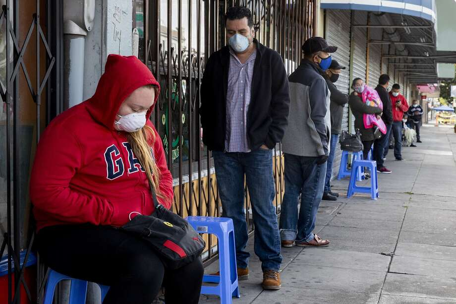 Francisco Montero (center) of Richmond wears a mask while waiting with other in a long line outside of Terra Nova Clinic in the Fruitvale neighborhood of Oakland, Calif. Tuesday, May 12, 2020. Dr. Carlos Ramirez runs Terra Nova Clinic and serves only the uninsured with most of his clients being of the undocumented, working poor. He charges an $80 flat fee for a consultation and when they can�t afford the care, he often treats them for free. Dozens of patients line up outside of his clinic three days a week to reserve a spot since he operates as first come, first serve. With many small clinics serving such communities closed during the pandemic, Ramirez now sees clients from as far as Eureka, desperate for care that is often put off far too long because they can�t afford consistent care. He doesn�t have testing for the coronavirus, but is screening patients and has written about 50 letters needed by patients to get tests. Photo: Jessica Christian / The Chronicle