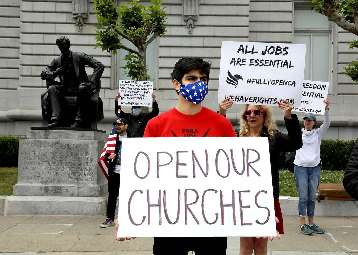 """Enrique Brenes holds a sign stating, """"Open Our Churches,"""" during a rally in front of City Hall calling for Gov. Newsom to immediately reopen California completely in San Francisco, Calif., on Saturday, May 9, 2020. Protesters argued they've been stripped of their rights."""