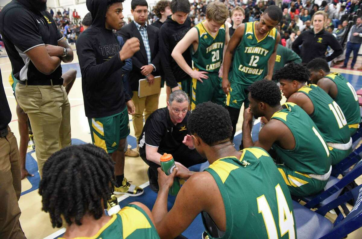 Trinity Catholic coach Brian Kriftcher talks with his players during a time out during a FCIAC tournament game against Ridgefield last season in Wilton.