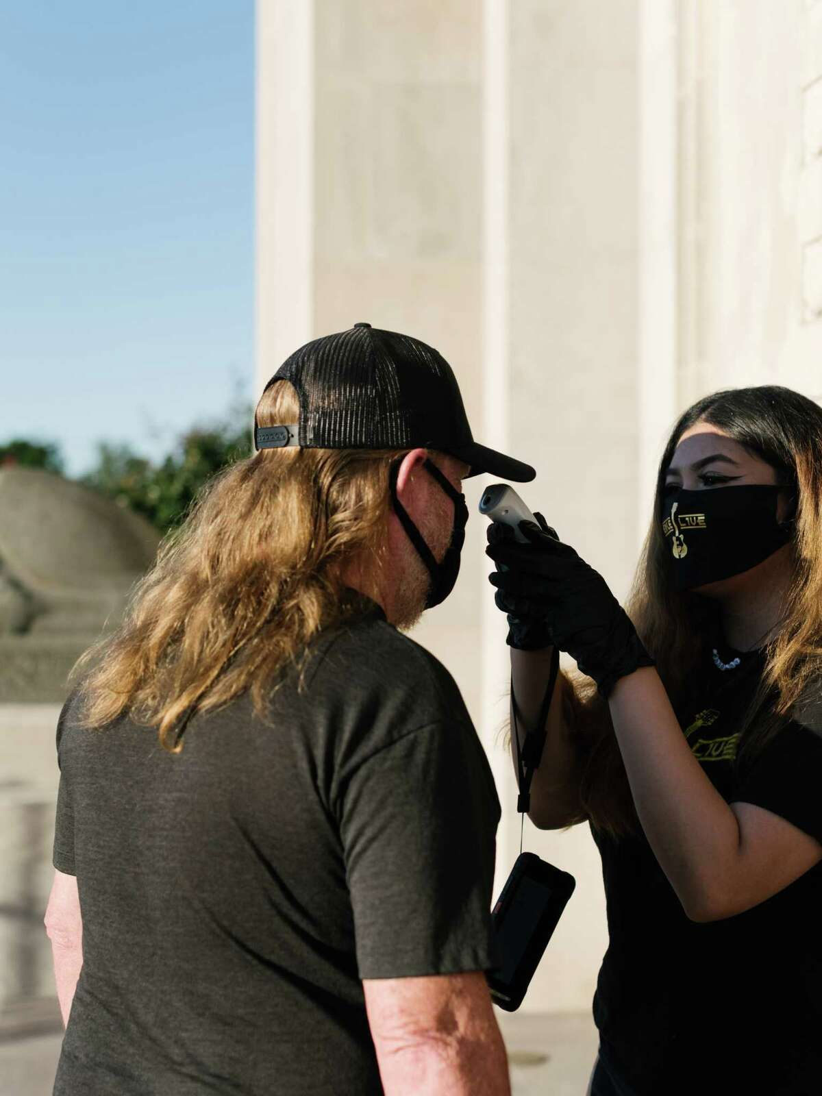 An attendee has their temperature checked outside the venue for Travis McCready's concert in Fort Smith, Ark., May 18, 2020. Fans who had to have their temperatures taken and wear masks for the show said it was worth it for the experience of hearing live music again. (Rana Young/The New York Times)