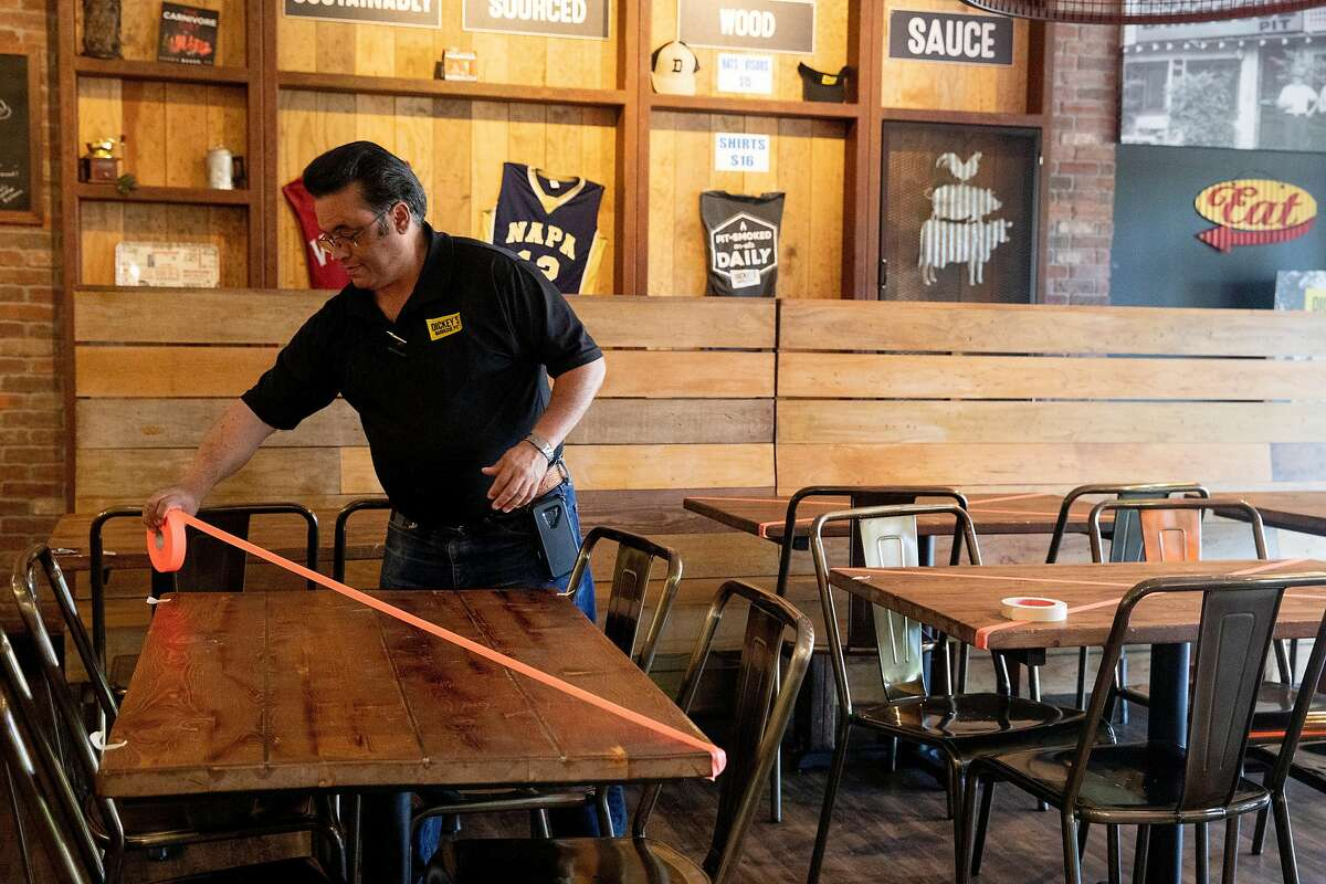 Dickey's Barbecue Pit owner Rene Bassett places tape on tables after customers asked to dine indoors at his restaurant in Napa, Calif. Tuesday, May 5, 2020. Bassett planned to open his restaurant to in-house and outdoor seating Tuesday but his plans were put on pause by the local health inspector.