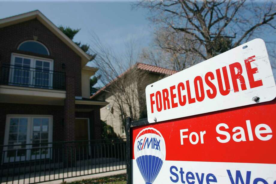 In this April 4, 2010 file photo, a foreclosure sign sits atop a for sale sign in front of a single-family home tops the for sale sign in Denver. Barack Obama's road to re-election is lined with lots of boarded-up homes. While the high unemployment rate dominates talk in Washington, for many 2012 voters the housing crisis may well be a more powerful manifestation of the sick economy. And, in an unfortunate twist for Obama, the housing problem is at its worst in many of the battleground states that will be decisive in determining whether the president gets another term. (AP Photo/David Zalubowski, File) Photo: David Zalubowski, STF / AP / AP