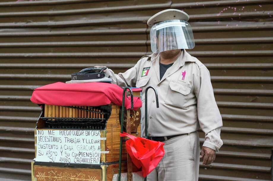 Un organillero que porta una careta protectora contra el coronavirus pide cooperación a transeúntes el sábado 16 de mayo de 2020, en la Ciudad de México. Photo: Christian Palma /Associated Press / Copyright 2020 The Associated Press. All rights reserved.