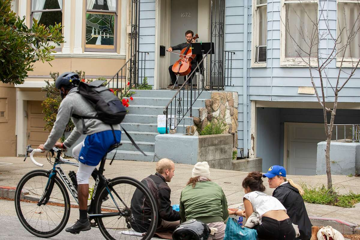 Saul Richmond-Rakerd plays the cello at his porch on Thursday, May 14, 2020, in San Francisco, Calif. Richmond-Rakerd, 28, is a professional classical cellist. Almost all his work has dried up with live music events canceled, due to the coronavirus pandemic. To entertain his neighbors and make some money, he plays the cello on his porch. His donation box is outside his home on the sidewalk along Page Street, which is one of the streets that's closed to through traffic.