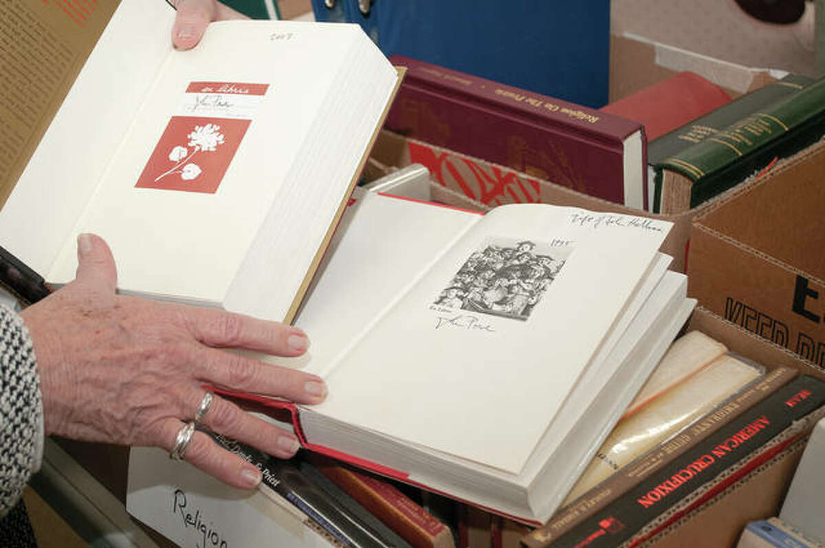 The late John Power kept meticulous records of his book collection and owned several signed books with personal notes from authors. Debbie Fry holds open one of Power's books.