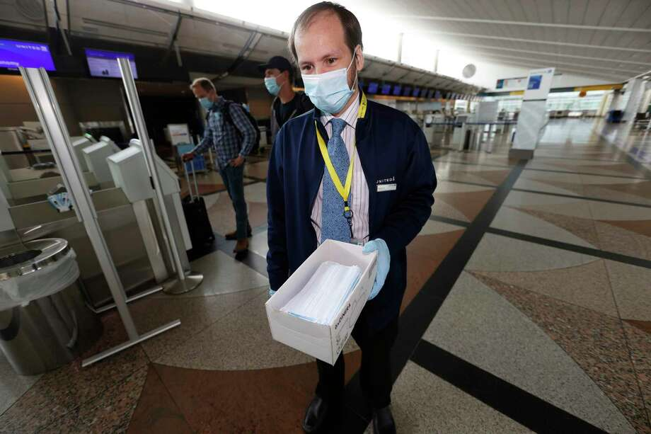 A United Airlines agent carries a box of face masks for travelers in the main terminal of Denver International Airport as it gets back to life with the easing of restrictions to check the spread of the new coronavirus recently. Photo: David Zalubowski / Associated Press / Copyright 2020 The Associated Press. All rights reserved.