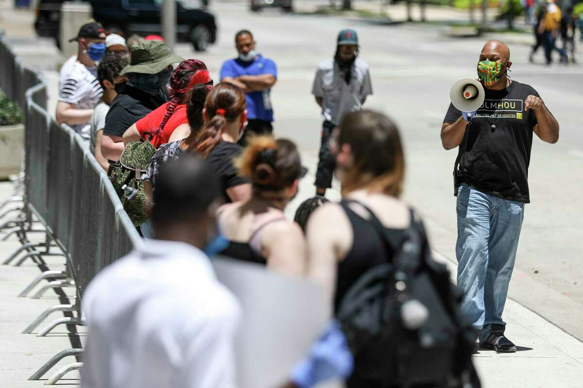 Ashton Woods, right, a co-founder of Black Lives Matter Houston, leads a protest over the shooting death of Rayshard Scales on Monday, May 18, 2020, at HPD headquarters in Houston. Scales was shot by police at a bus stop near the intersection of Scott Street and Corder Street and later died at the hospital. The fatal shooting was one of at least five involving Houston police since April 21.