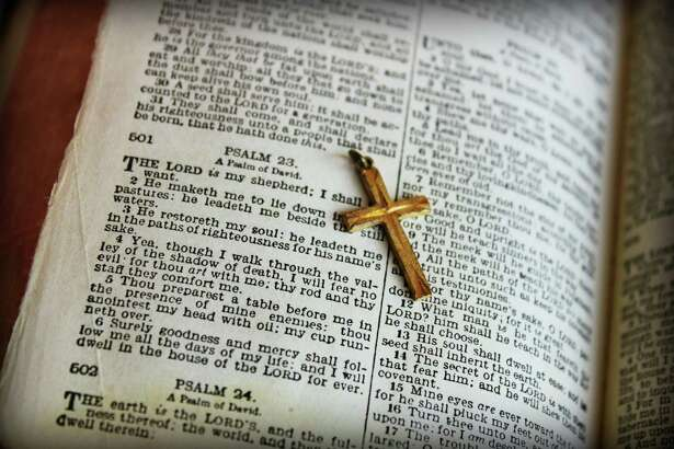 A vintage Bible opened to the 23rd Psalms with a golden cross.