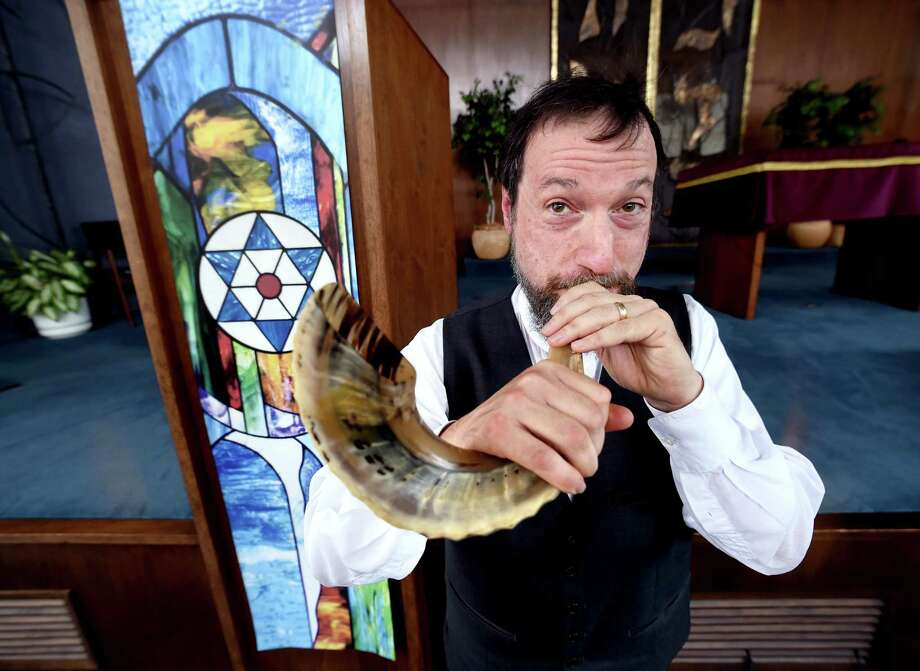 Rabbi Jon-Jay Tilsen demonstrates blowing a shofar at Congregation Beth-El Keser Israel in New Haven in 2017. Photo: Arnold Gold / Hearst Connecticut Media File / New Haven Register