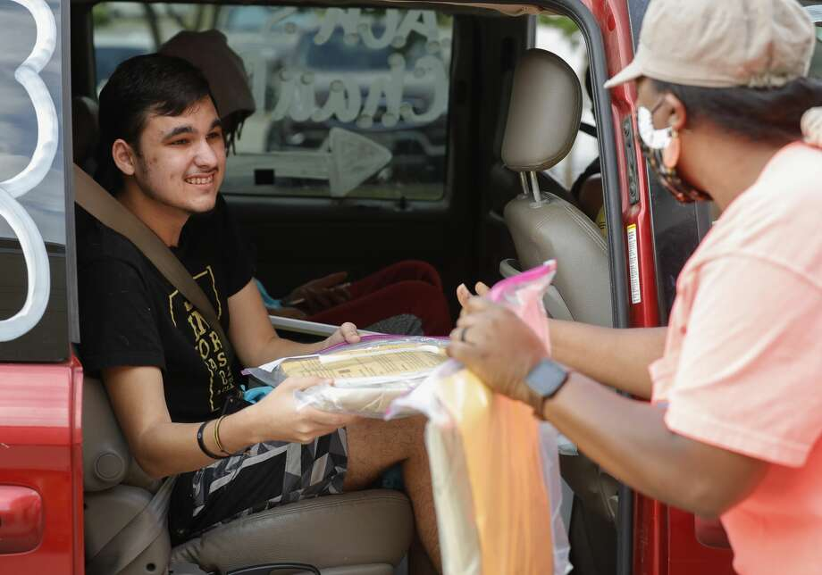 Zach Calderon receives his graduation packet as more than 900 members of the graduating class of Conroe High School took part in a drive-thru parade to pick up their caps and gowns along with other items, Wednesday, April 20, 2020, in Conroe Photo: Jason Fochtman/Staff Photographer / 2020 ? Houston Chronicle