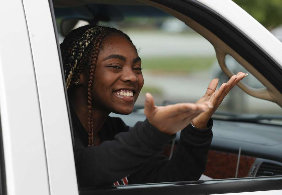Ahmaiha Brundidge blows kisses to a teacher after picking up her graduation packet as more than 900 members of the graduating class of Conroe High School took part in a drive-thru parade to pick up their caps and gowns along with other items, Wednesday, April 20, 2020, in Conroe Photo: Jason Fochtman/Staff Photographer / 2020 ? Houston Chronicle