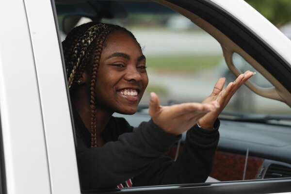 Ahmaiha Brundidge blows kisses to a teacher after picking up her graduation packet as more than 900 members of the graduating class of Conroe High School took part in a drive-thru parade to pick up their caps and gowns along with other items, Wednesday, April 20, 2020, in Conroe