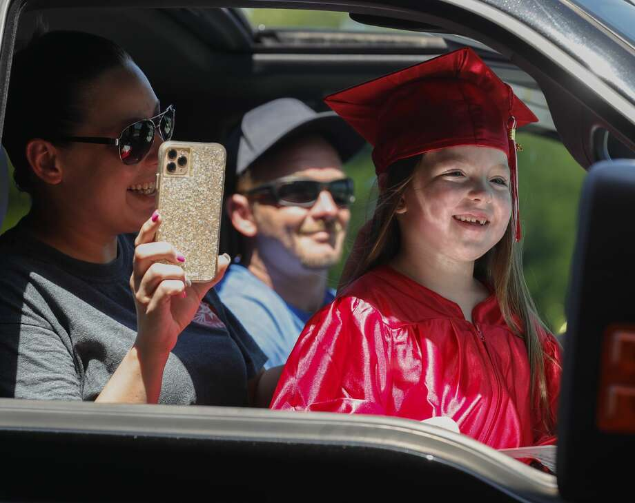 Makenzie Strickland smiles wearing a graduation cap and gown as 150 kindergarten students from Greenleaf Elementary School took part in a drive-thru graduation, Tuesday, May 19, 2020, in Splendora. Photo: Jason Fochtman/Staff Photographer / 2020 ? Houston Chronicle
