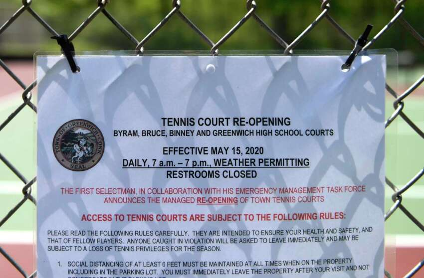 A sign is posted at the tennis courts at Greenwich High School in Greenwich, Conn. Sunday, May 17, 2020. The town's tennis courts reopened on May 15 with many restrictions including mandatory social distancing and no doubles play.