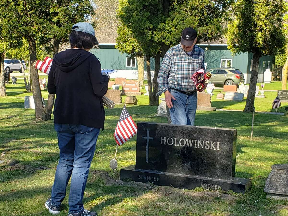 Donna and Dan Korzeniewski placed flags with the Catholic War Veterans Duchon Post 1847 at Mount Carmel Cemetery on Maple Street and Merkey Road in Manistee Wednesday morning.