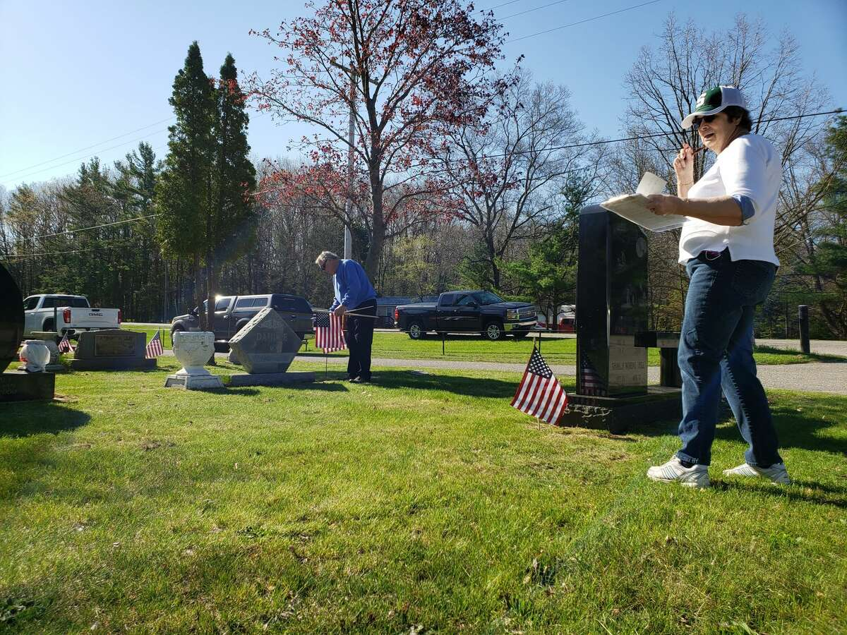 Betsi Rothrock leads a group of volunteers with the Catholic War Veterans Duchon Post 1847 in placing flags at Mount Carmel Cemetery and Trinity Cemetery on Maple Street and Merkey Road in Manistee Wednesday morning.