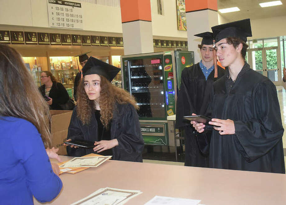 The Doyle triplets — Isabella, Mathiew and Jakob — pick up their diploma, cords and awards during Tuesday's graduation drive-thru event at Edwardsville High School. The event will continue each day through Friday. Photo: Matt Kamp | The Intelligencer