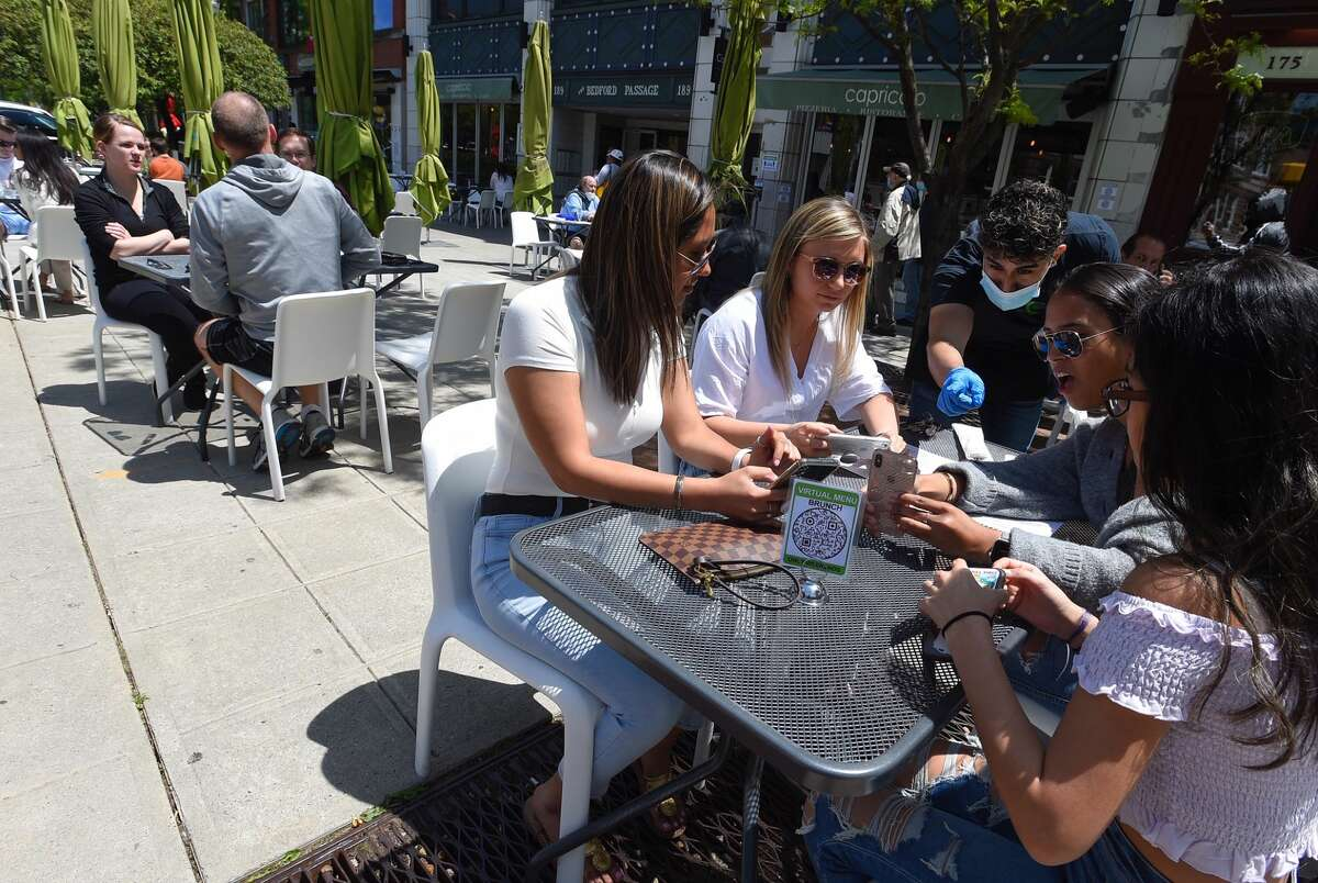 Patrons set up the iPhones with a virtual menu at Capriccios in Stamford. The restaurant is one of several to reopen with outdoor dining service.