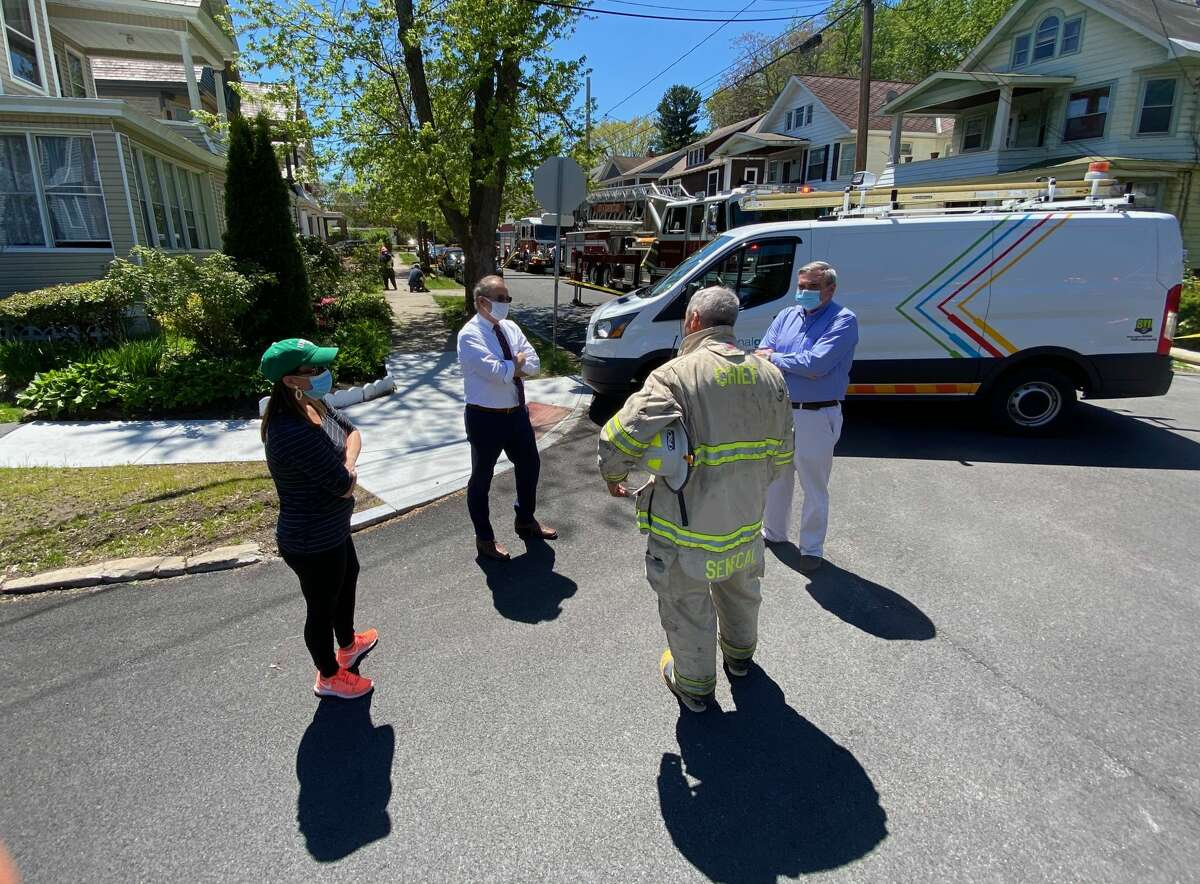 Schenectady County, second from left, and Mayor Gary McCarthy, right, confirm with officials after a fatal blaze Wednesday afternoon at 203 Elmer Ave., in Schenectady. A man's body was found in the building after a series of explosions and a fire occurred.