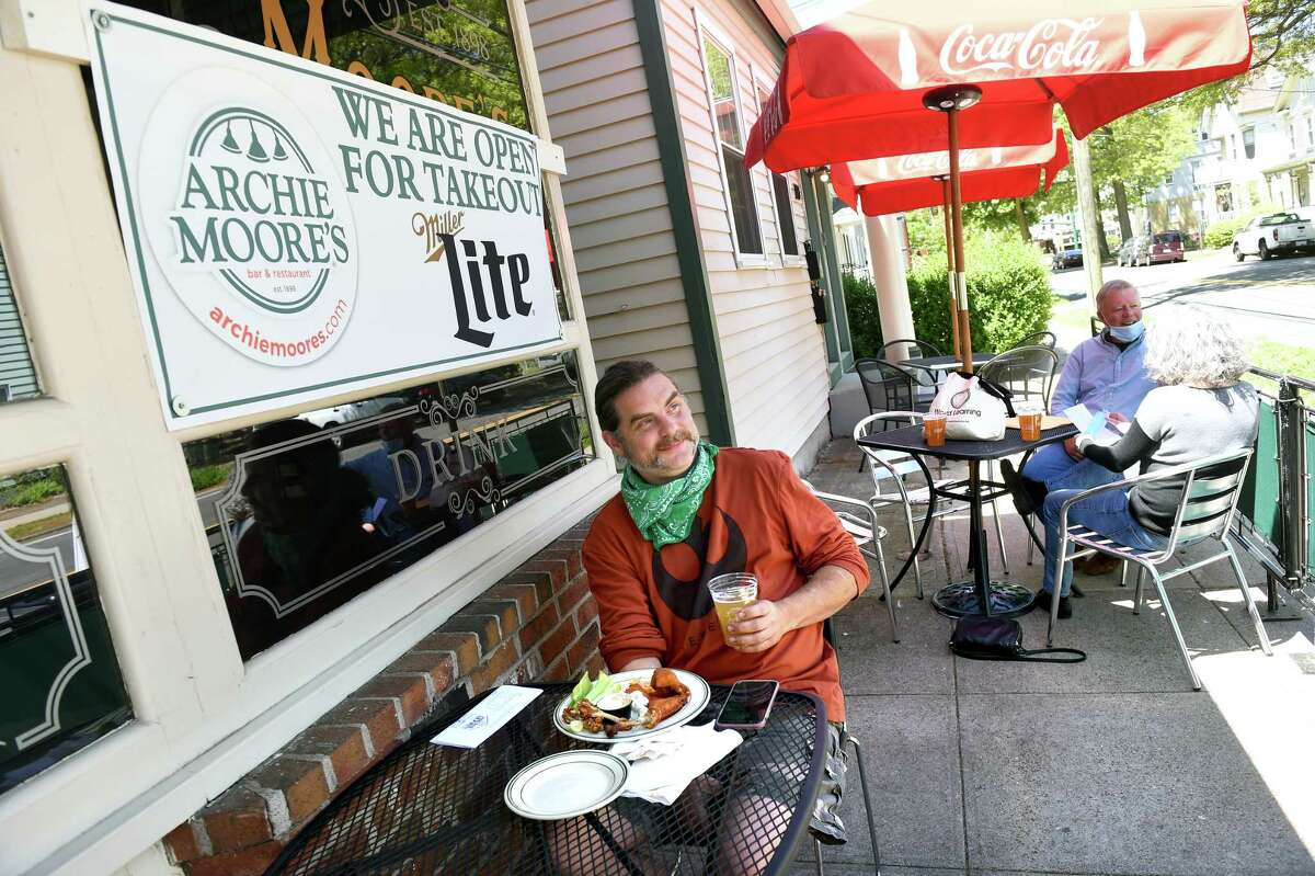 Rob Rintoul of Hamden enjoys Buffalo wings and a beer at Archie Moore's Bar & Restaurant's outdoor seating on Willow Street in New Haven on the first day of the phased reopening of businesses in Connecticut on May 20, 2020.